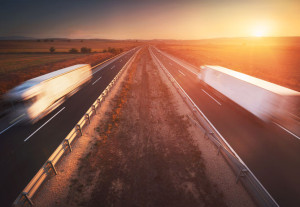 Trucks in the highway, dramatic sunset, motion blur. Cargo, transportation concept