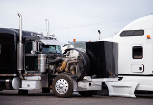 Big rig black semi truck tractor with open hood prepare engine t