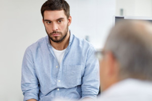 young male patient talking to doctor at hospital