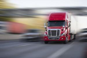 Bright red modern big rig semi truck with semi trailer move with
