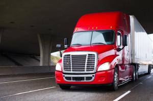 Bright red modern big rig semi truck with dry van trailer runnin
