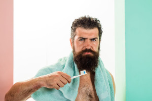 Serious bearded man brushing teeth. Oral care. Tooth brush. Tooth paste. Cleaning teeth. Morning treatments. Morning routine. Health care. Dental hygiene. Whitening teeth. Isolated.